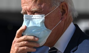 Joe Biden adjusts his double mask as he walks off the plane in Detroit, Michigan, on October 16, 2020.