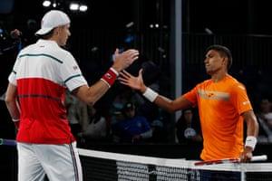 John Isner (left and Thiago Monteiro meet at the net after their match.