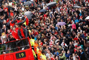 Manchester United fans line the city's rain-soaked streets to cheer their team during a parade of the Premier League trophy. The bus bears the number 19 to mark the number of times the club has won the title.