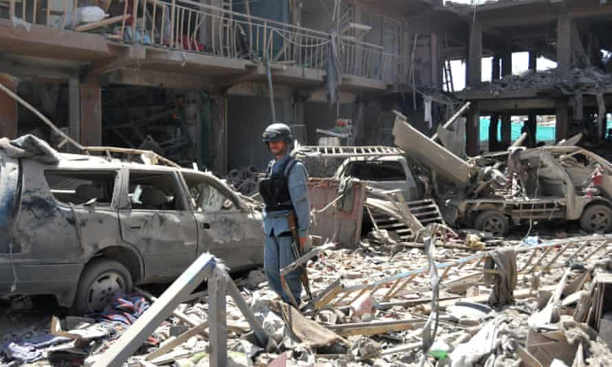 An Afghan policeman stands guard at a blast site in Kabul