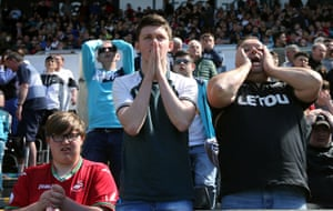 Swansea fans, dejected after their team loose 2-1 to Stoke and relegation is confirmed at the Liberty Stadium.