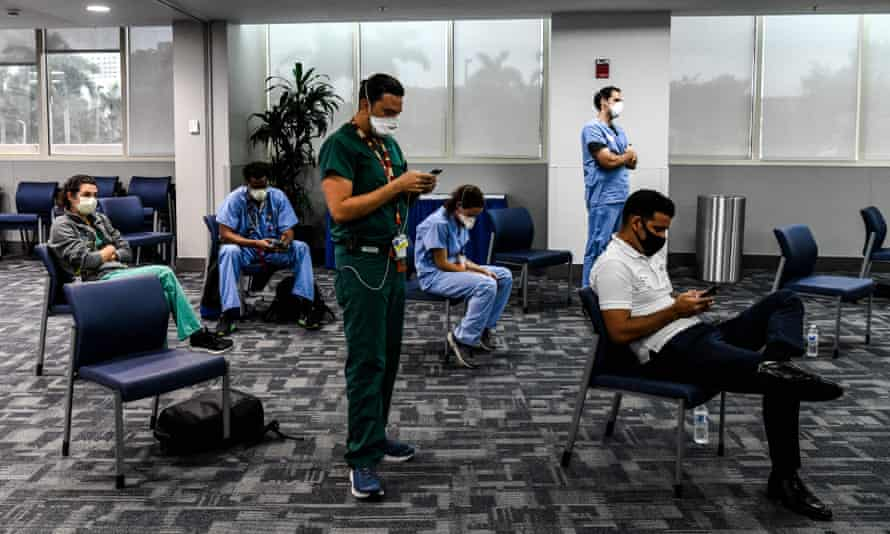 Students and doctors of Medical Science listen to the governor of Florida during a press conference to address the rise of coronavirus cases in the state, at Jackson Memorial Hospital in Miami, on July 13, 2020