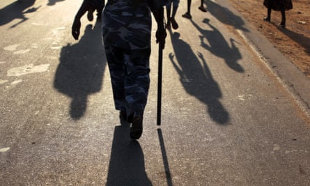 A police officer walks in a pro-independence march in Juba, South Sudan
