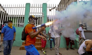 A masked protester shoots off his homemade mortar in the Monimbo neighborhood during clashes with police, in Masaya, Nicaragua.