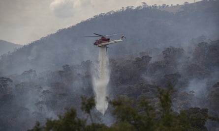 A helicopter water-bombs a Canberra fire in February