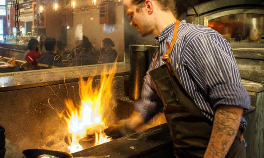 man cooking over wood in kitchen