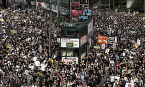 Tens of thousands of people pack a Hong Kong street while marching to Hong Kong government headquarters to protest the Hong Kong government's plans to enact an anti-subversion bill.