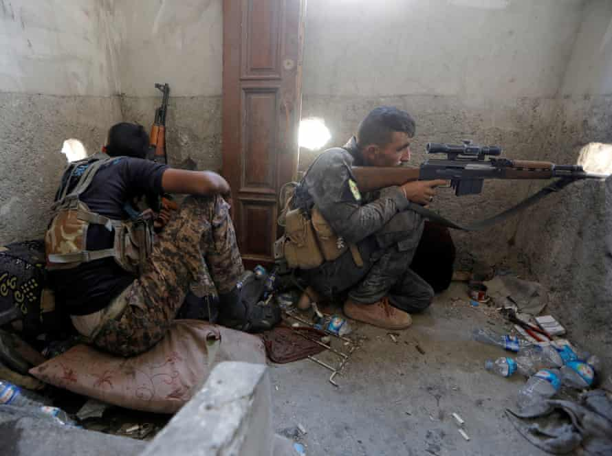 A Syrian Democratic Forces sniper aims his gun at Isis fighters in the old city of Raqqa, on 19 August