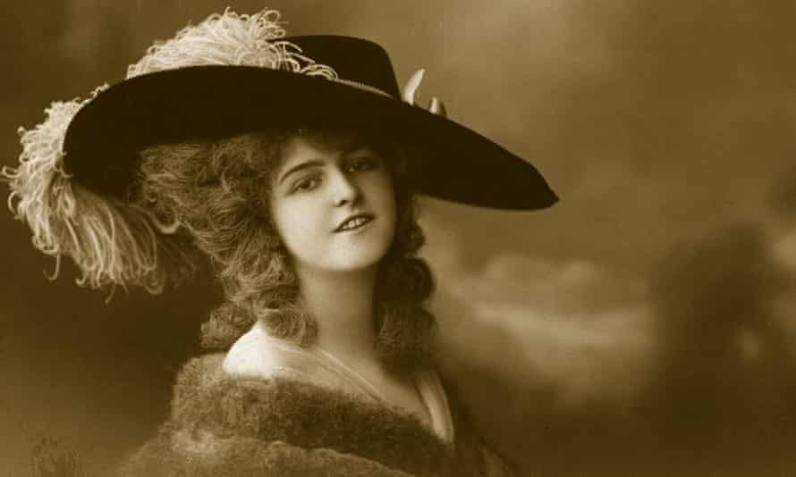 A woman wears a wide-brimmed hat with ostrich feather trimming in a sepia photo from around 1910