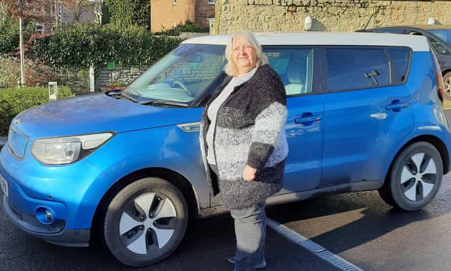 Sue Peachey, 57, with her new electric car, which she bought after attending the UK's first climate assembly