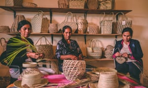 Indigenous Qom people weave baskets with palm leaves
