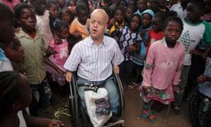 Professor Tom Shakespeare (left) with disabled Marta Joao Lucas (right) with a group of school children at Escola Primaria 25 de Setembro in Buzi, Mozambique