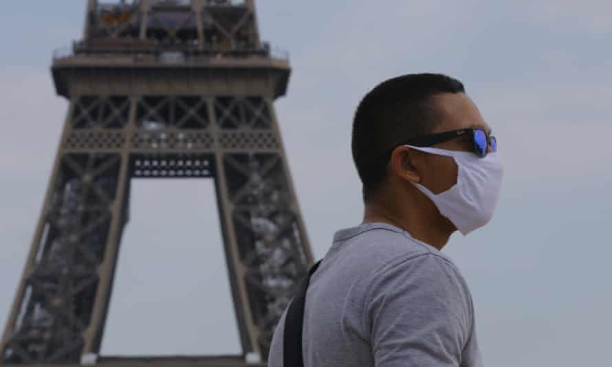 Man wearing face mask in front of Eiffel Tower