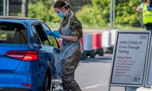 A soldier administers a coronavirus test to a car passenger