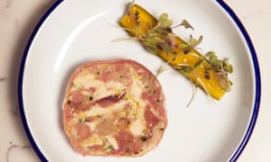 A round of pink and white terrine with a strip of halved cucumber by the side on a round white plate with a blue rim