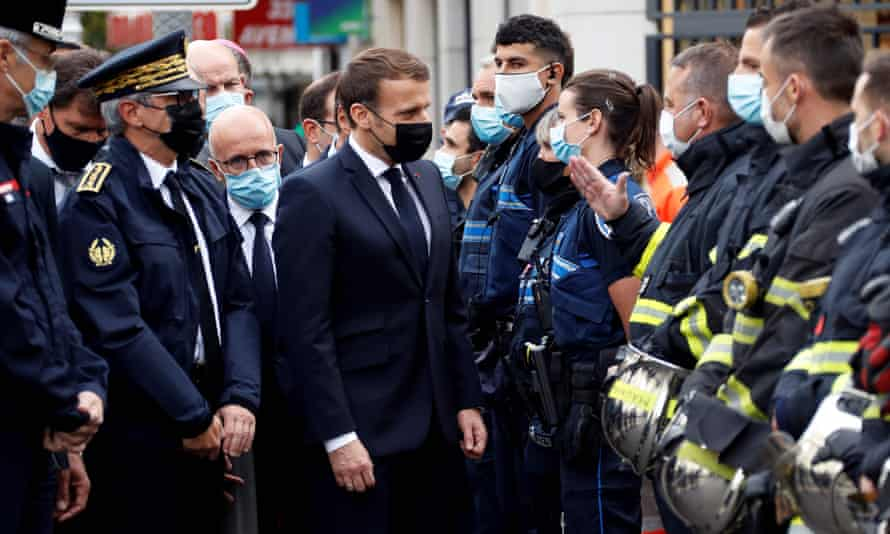 Emmanuel Macron (4th-L) talks to emergency workers at the scene of the attack.