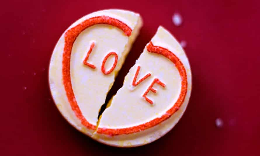 """A candy heart with the word """"Love"""" on it split down the middle"""