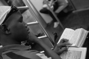 A young man reads the Koran on the Uptown 6 train in Manhattan, New York