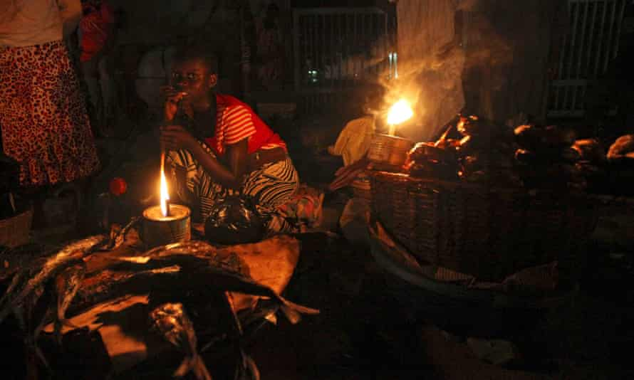 A woman sells fish by lantern light in Lagos, Nigeria.