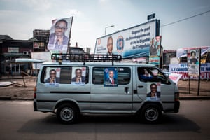 A campaign car is driven past political billboards
