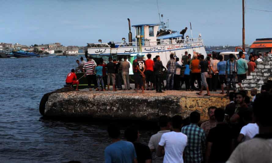 People gather along the Mediterranean during the search for victims in Al-Beheira, Egypt on Wednesday