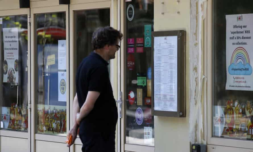 A man looks at a menu of a closed restaurant in London.