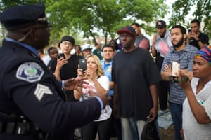 Neighborhood residents film a police officer with cellphones while speaking about police mistreatment in Camden, New Jersey, on 18 May 2015.