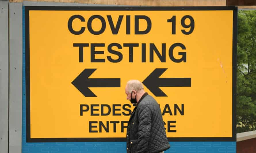 A man walks past a sign for a Covid-19 test centre