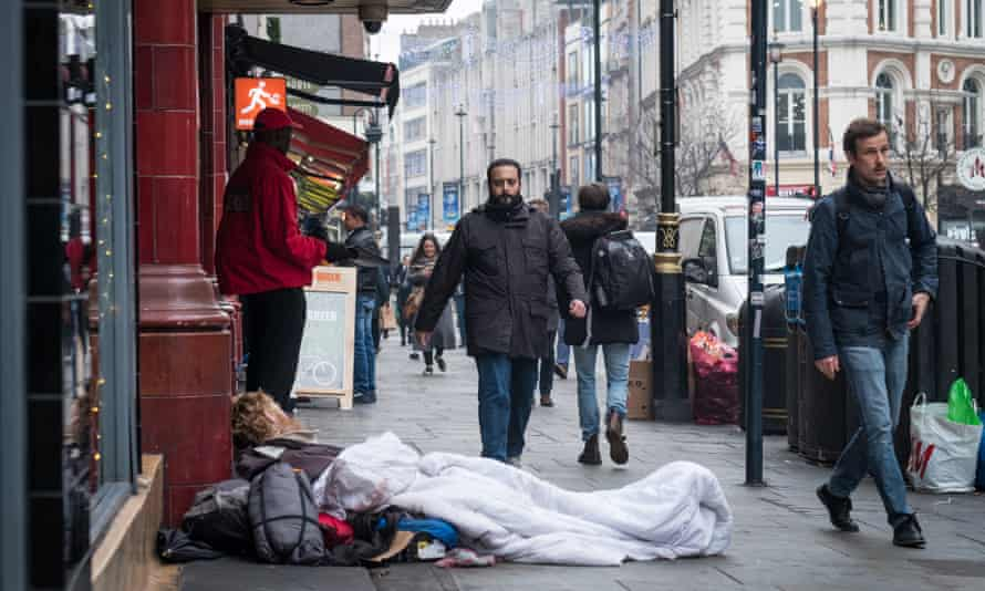 People walk past a homeless man sleeping outside Leicester Square underground station in London last week