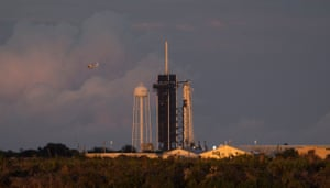 A NASA helicopter flying past a SpaceX Falcon 9 rocket