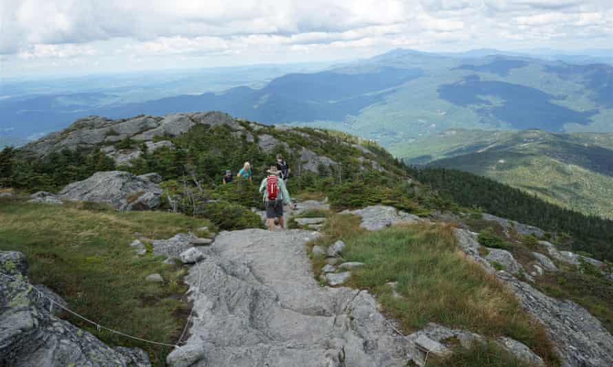 Hiker beginning to descend the summit of Camels Hump in Huntington, Vermont US.