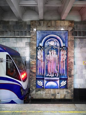 A ceramic mural is revealed as a train rolls out of Tashkent station