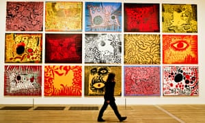 Woman walking in front of huge colourful painting by Yayoi Kusama