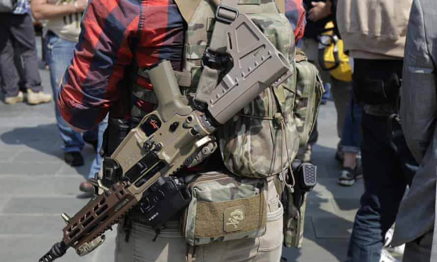 A man standing with members of Patriot Prayer and other groups supporting gun rights wears guns during a rally in Seattle. Patriot Prayer is a source of disagreement between leftwing and rightwing pro-gun groups.