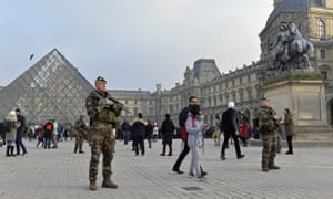 French military officers stand guard outside the Louvre, part of a huge national deployment for New Year's Eve.