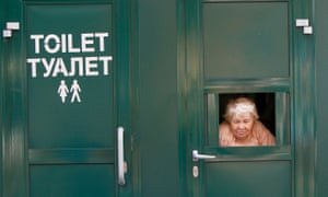 A cashier awaits clients as she sells tickets to a public toilet in central Kiev.