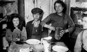 A meal of bread for a poverty-stricken family in Shadwell, East London, 1920.