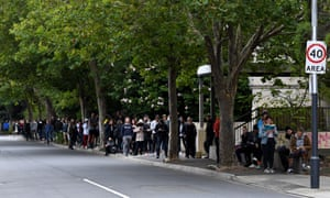 People queue outside a Centrelink, which delivers unemployment services, in Melbourne, Australia, 23 March 2020.