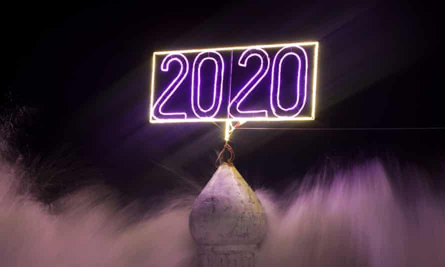 """An illuminated sign reading """"2020"""" is seen as waves hit the beach of Gaza shore ahead of new year celebrations in Gaza City,"""
