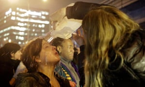 A woman gets water poured on her face after police pepper sprayed demonstrators attempting to stop traffic on Interstate 5 in Seattle, Washington