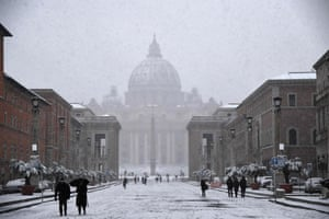 People walk on St Peter's square covered in snow at The Vatican.