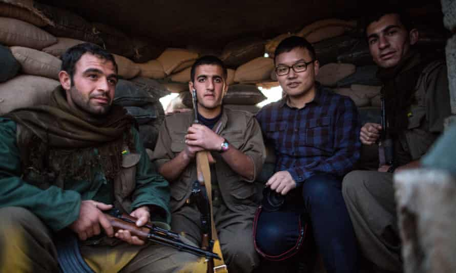 Chen Xu, a 29-year-old correspondent from China's state-run news giant Xinhua, poses for a photo with Kurdish fighters battling Islamic State in northern Iraq.