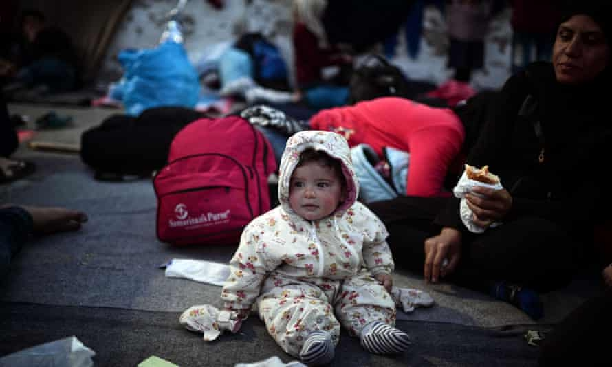 A baby sits on a blanket near his mother in the port in the town of Chios