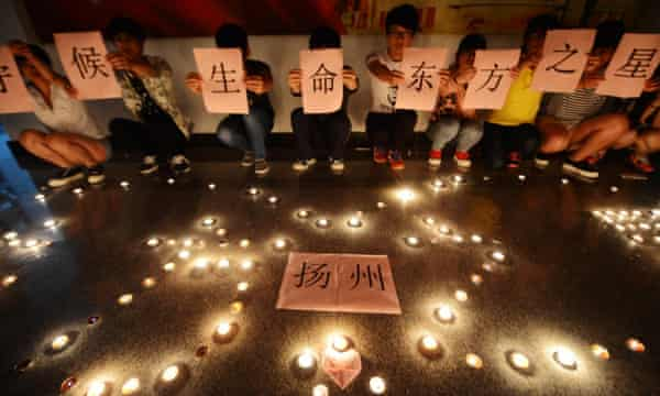 Students light candles and pray for victims of the Eastern Star at a Yangzhou college on Wednesday.