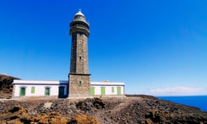 The Orchilla lighthouse on black volcanic  rock, ocean in background