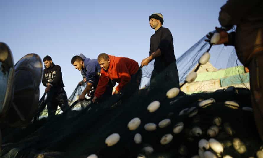 Palestinian fishermen prepare their net at the port in Gaza City