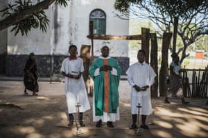 Tanzanian-born Father Valentin flanked by altar boys