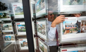 An estate agent adjusts a listing in the window of his store in Guildford, Surrey