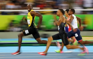 Jamaica's Usain Bolt looks back at Andre De Grasse of Canada as they compete in the semi-final of the men's 100m