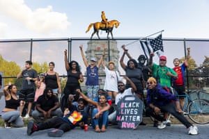 Black Lives Matter activists gather around the statue of the Confederate general Robert E Lee the night before it is scheduled to be removed in Richmond. Erected more than 130 years ago, it is the largest confederate statue in the US